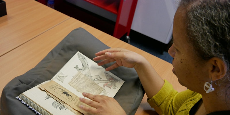 A woman is looking through a historical document with drawings in it, rested on a cushion.